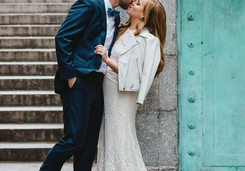 Groom kissing a bride in a wedding dress and jacket