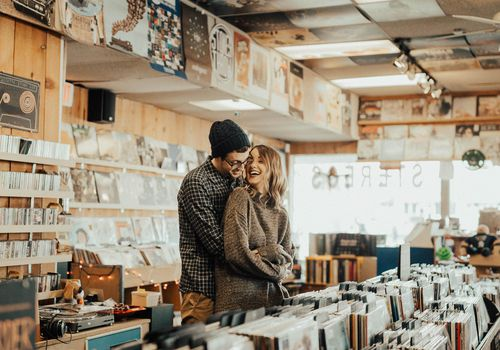 Man and woman embracing in record store