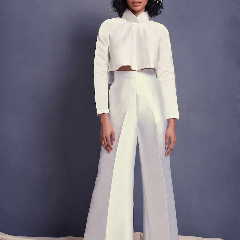 Model wearing Scorcesa bridal crop top and white wide leg trousers