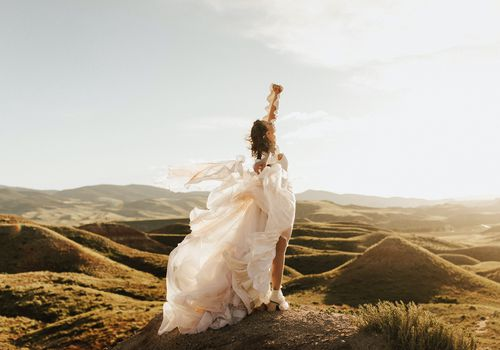 Bride in flowing wedding gown standing on hills with arm in the air