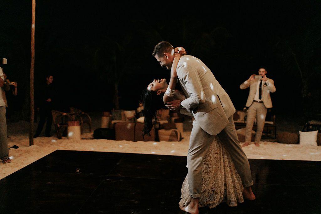 The groom dips the bride on the dancefloor
