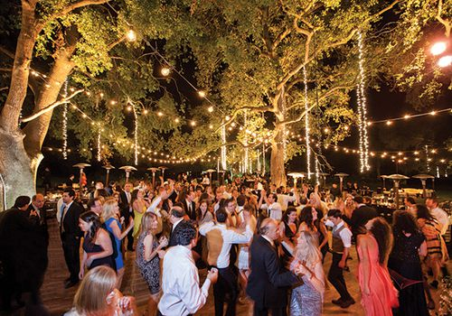 Guests dancing at outdoor evening wedding reception