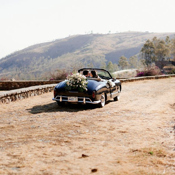 bride and groom in convertible with floral arrangement