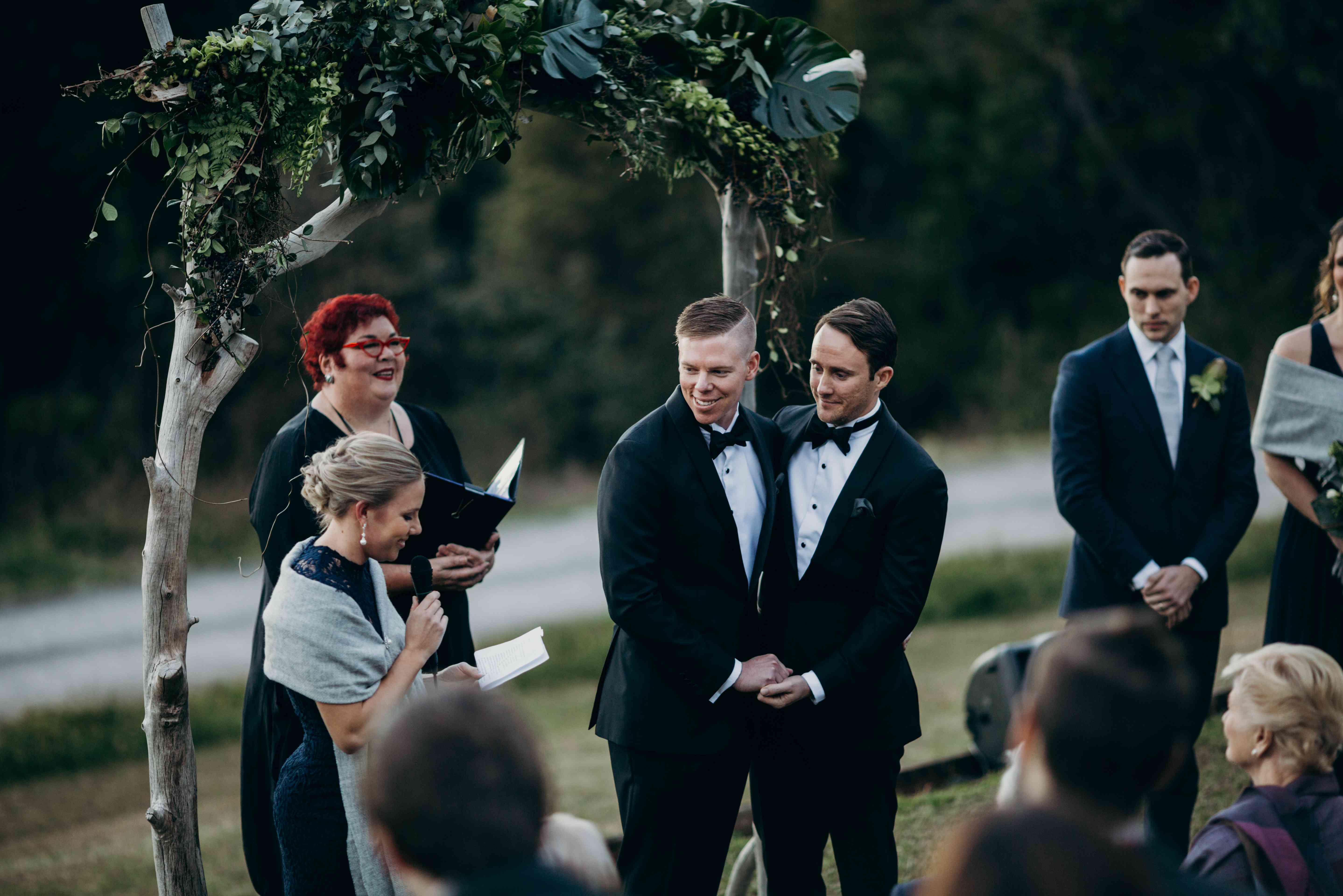 Grooms hold hands and embrace during wedding ceremony
