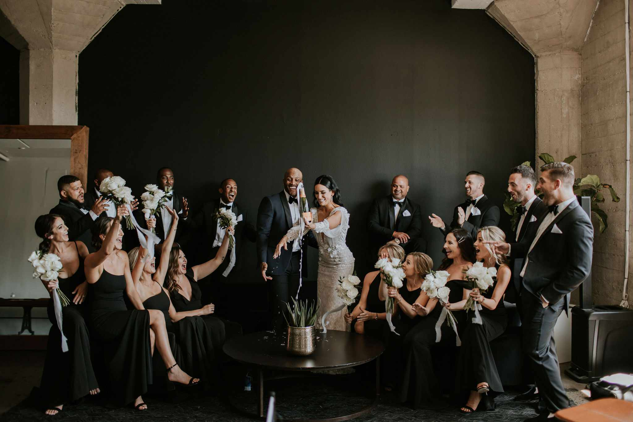 bride and groom popping champagne with wedding party