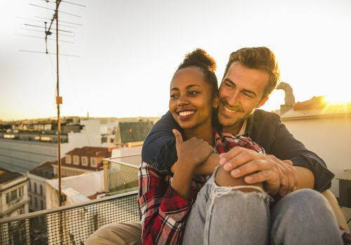 Couple cuddle outside on balcony