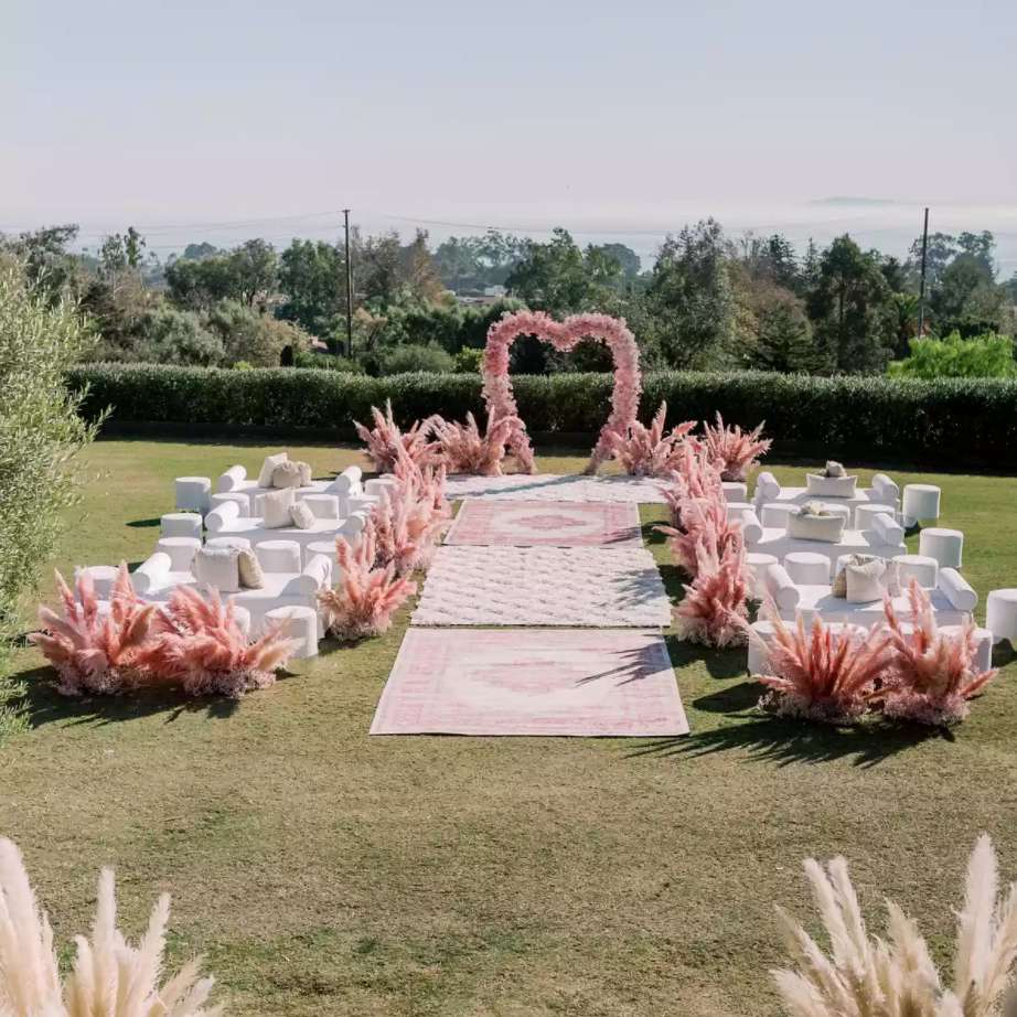 Pink heart-shaped altar lined with matching rugs and pampas grass aisle runners