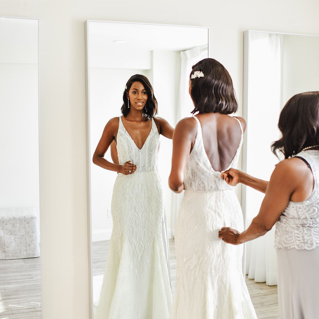 Bride looking in mirror while being zipped into dress