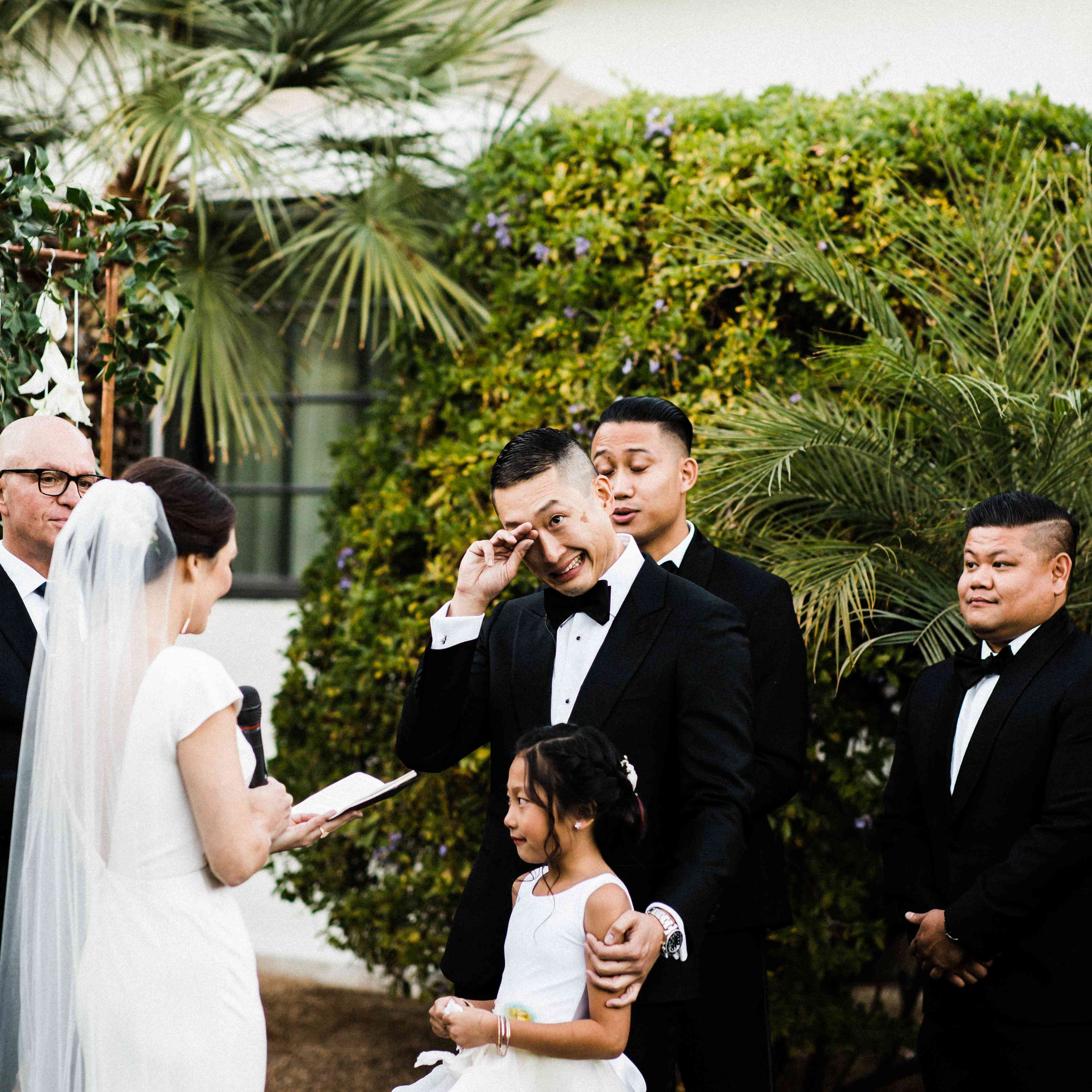 Groom getting emotional and wiping tears during wedding ceremony as bride reads her vows