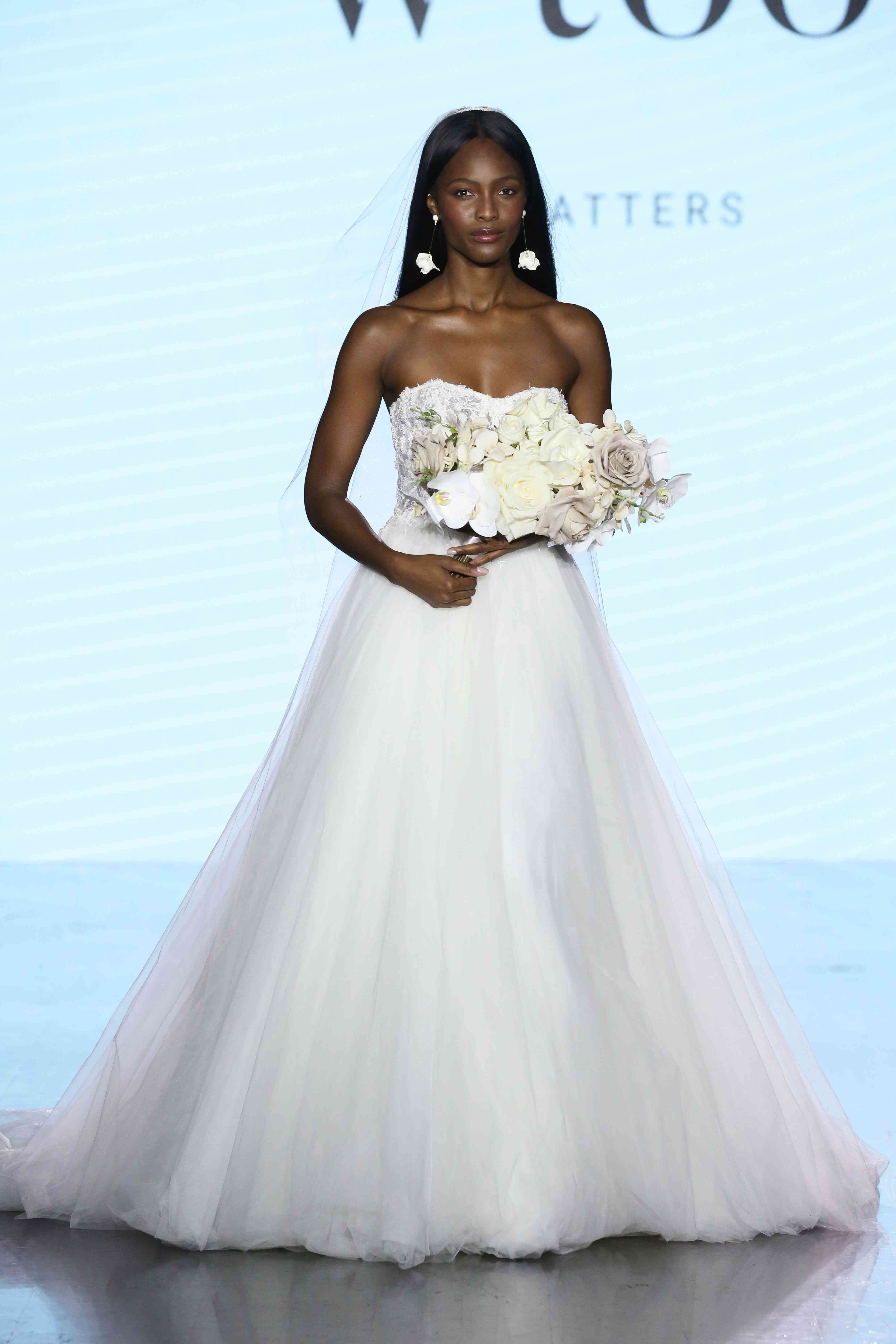 Model in strapless ballgown with a floral embroidered bodice and tulle skirt
