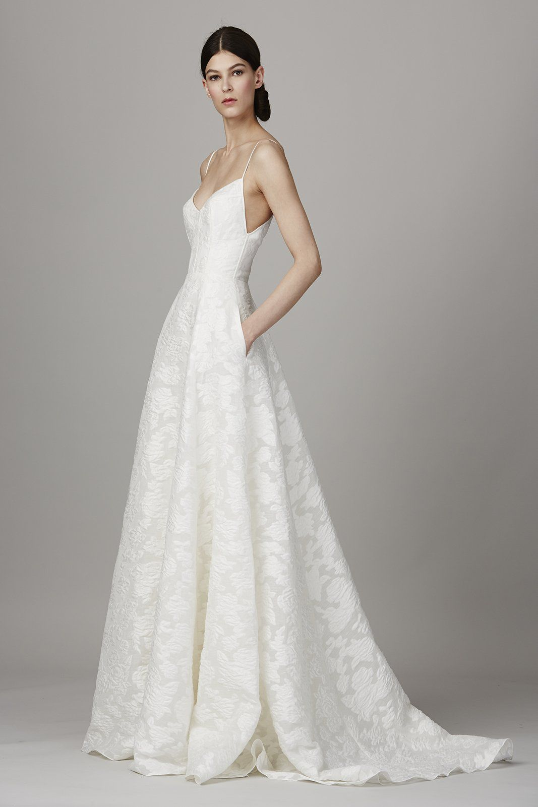 Model in spaghetti strap long white wedding gown with pockets