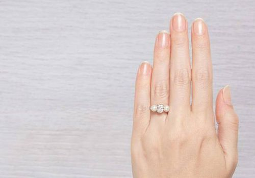 Woman's hand with pearl engagement ring