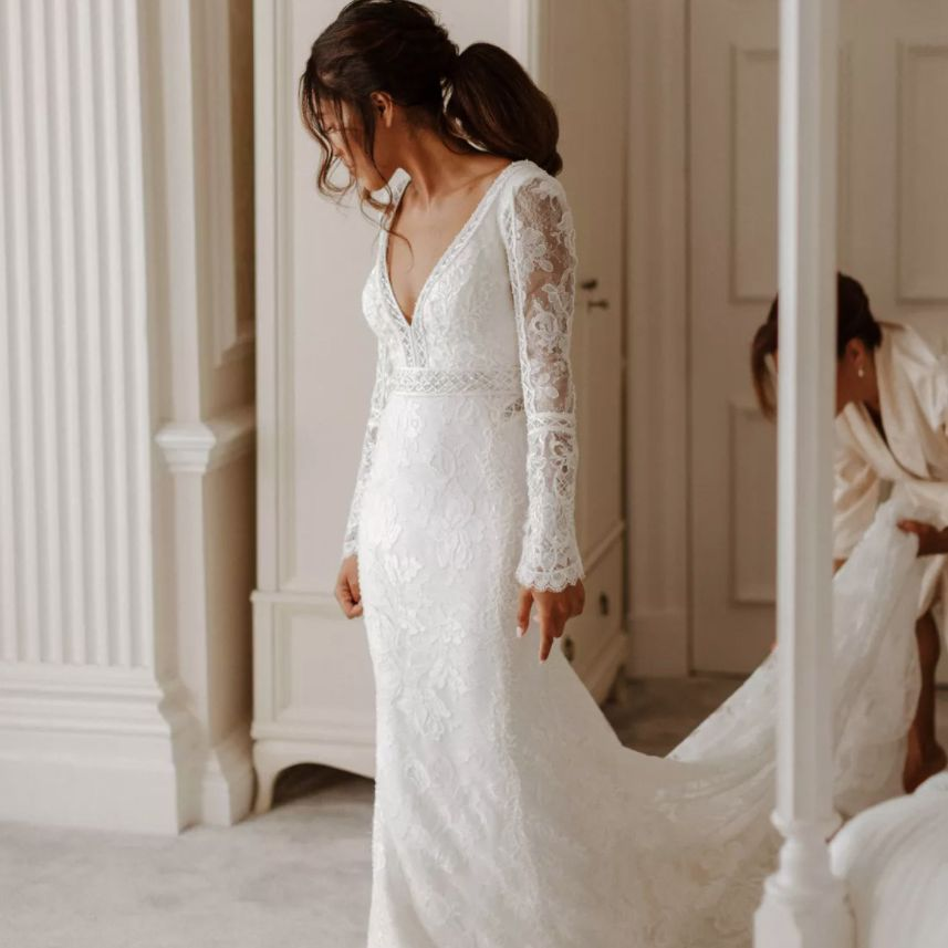 Bride with ponytail being zipped into dress