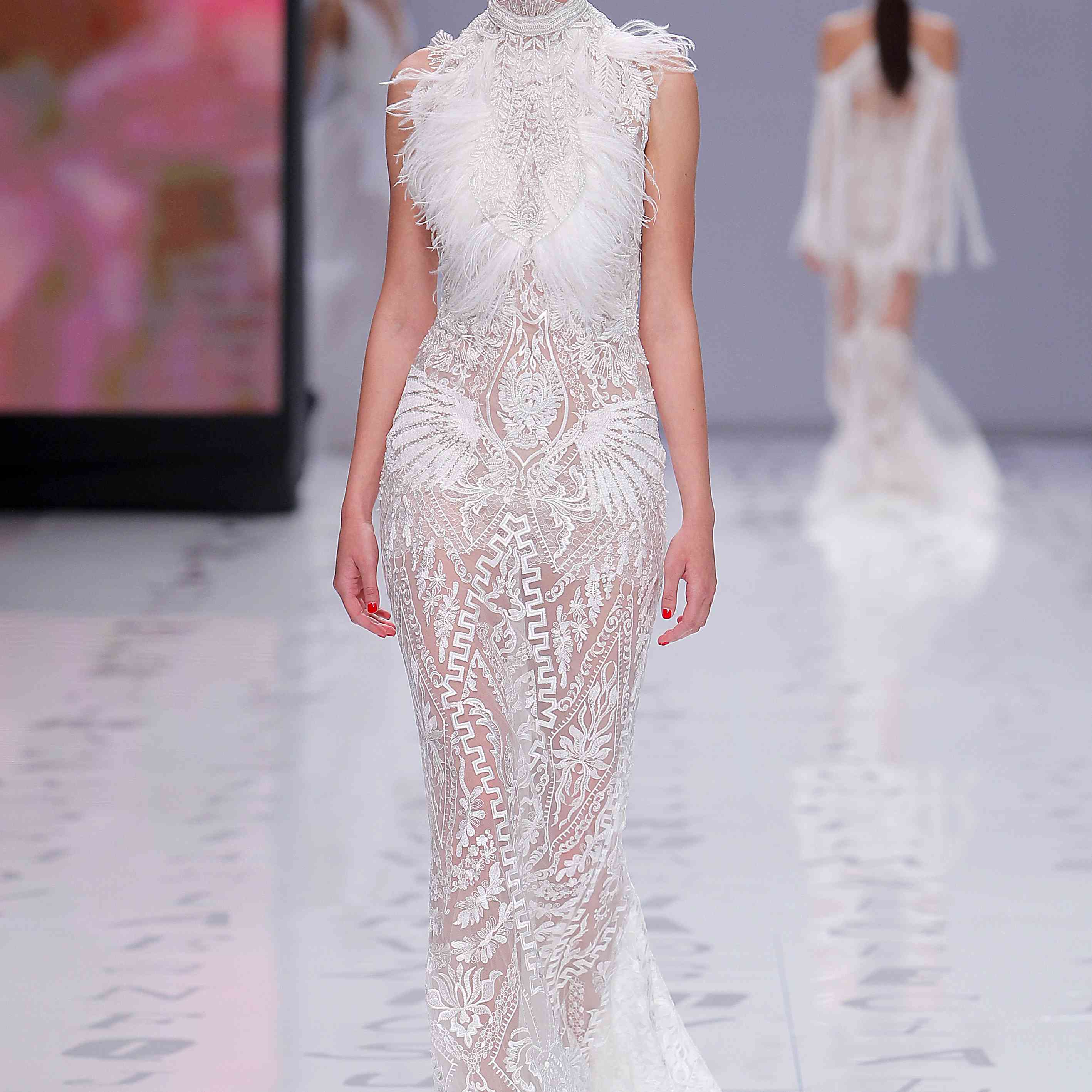 Model in a lace-embroidered sheer fitted sheath gown with a high neckline and feather details on the bodice