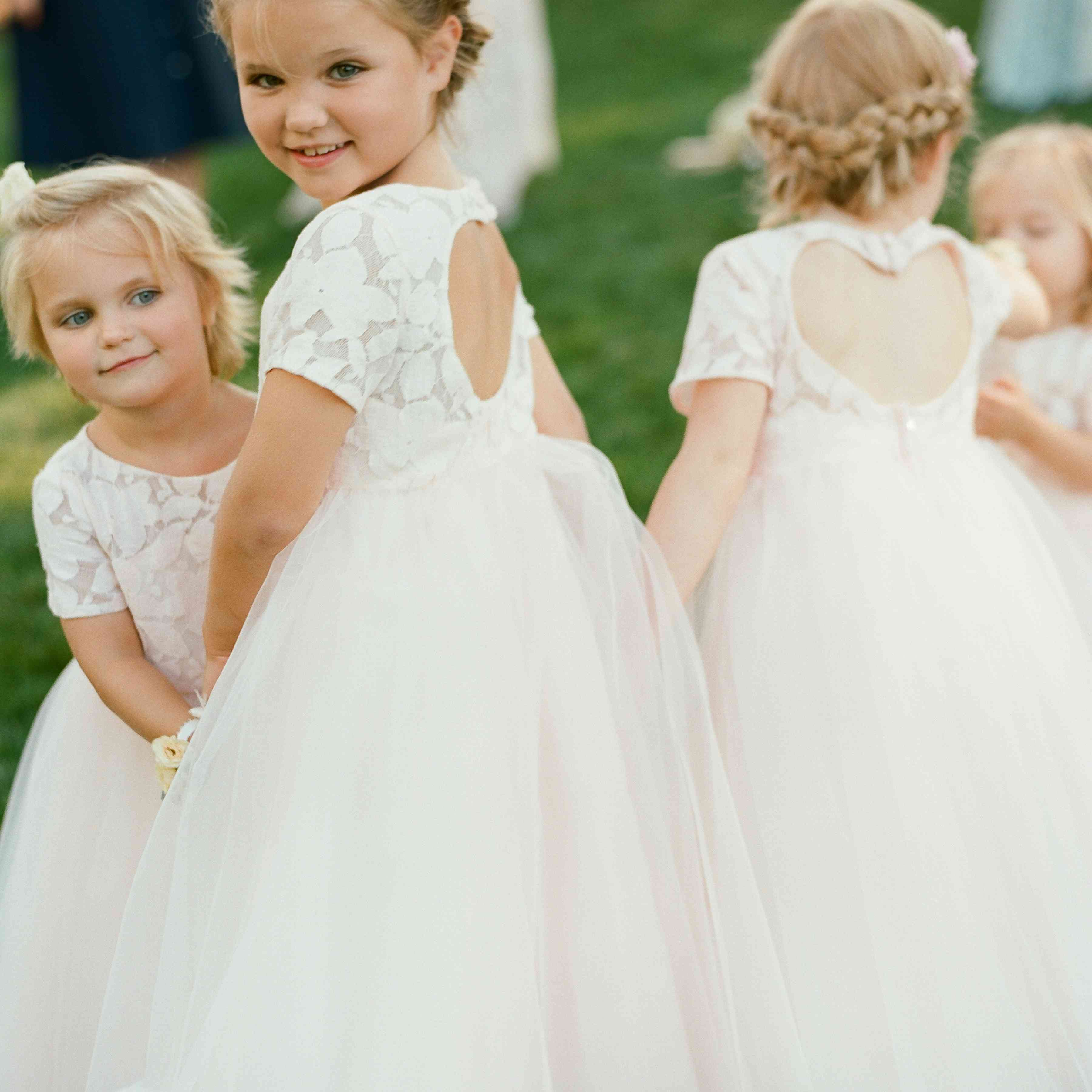 Four flower girls in white dresses with heart-shaped keyhole backs