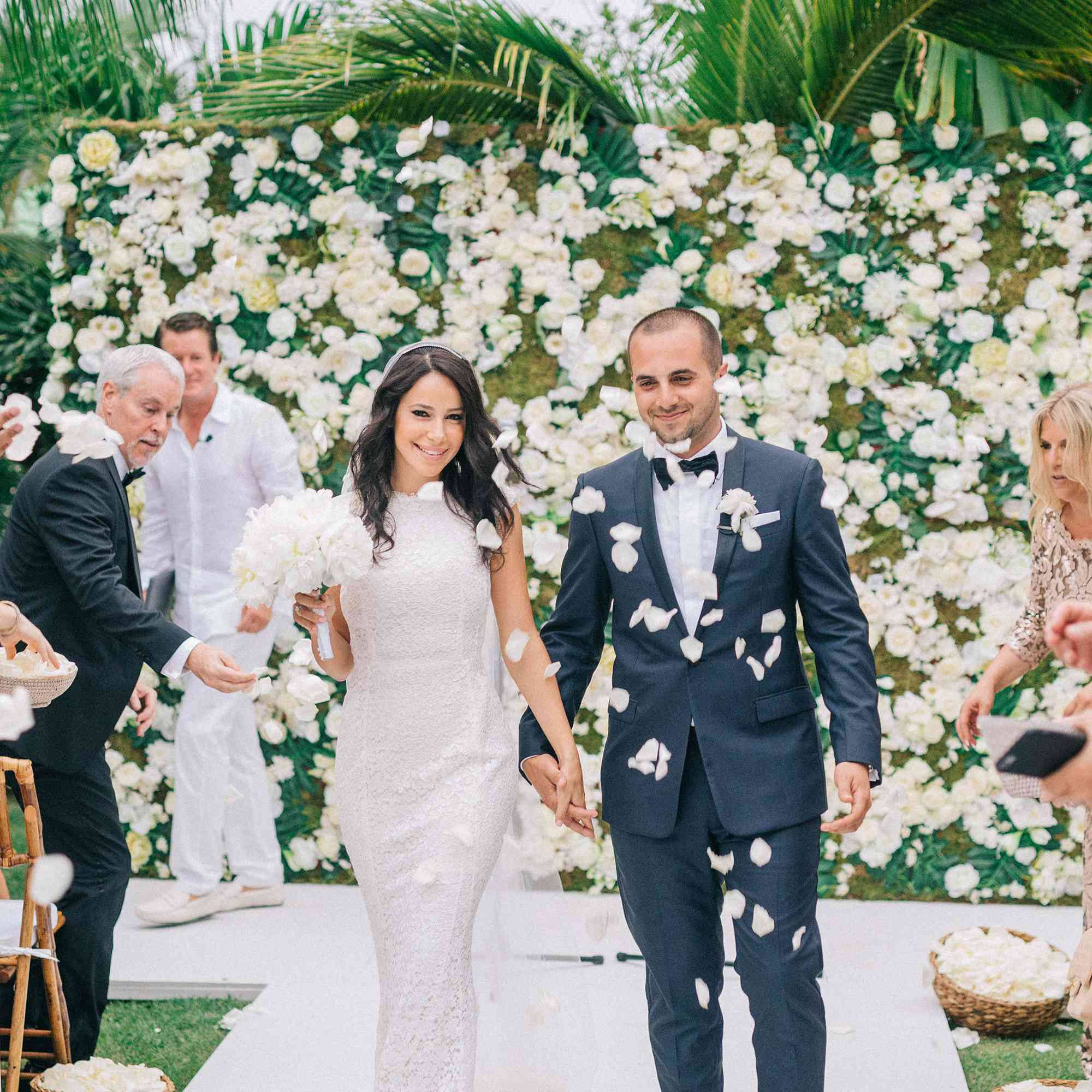 Newly married couple walking down aisle during recessional with flower wall altar in the background