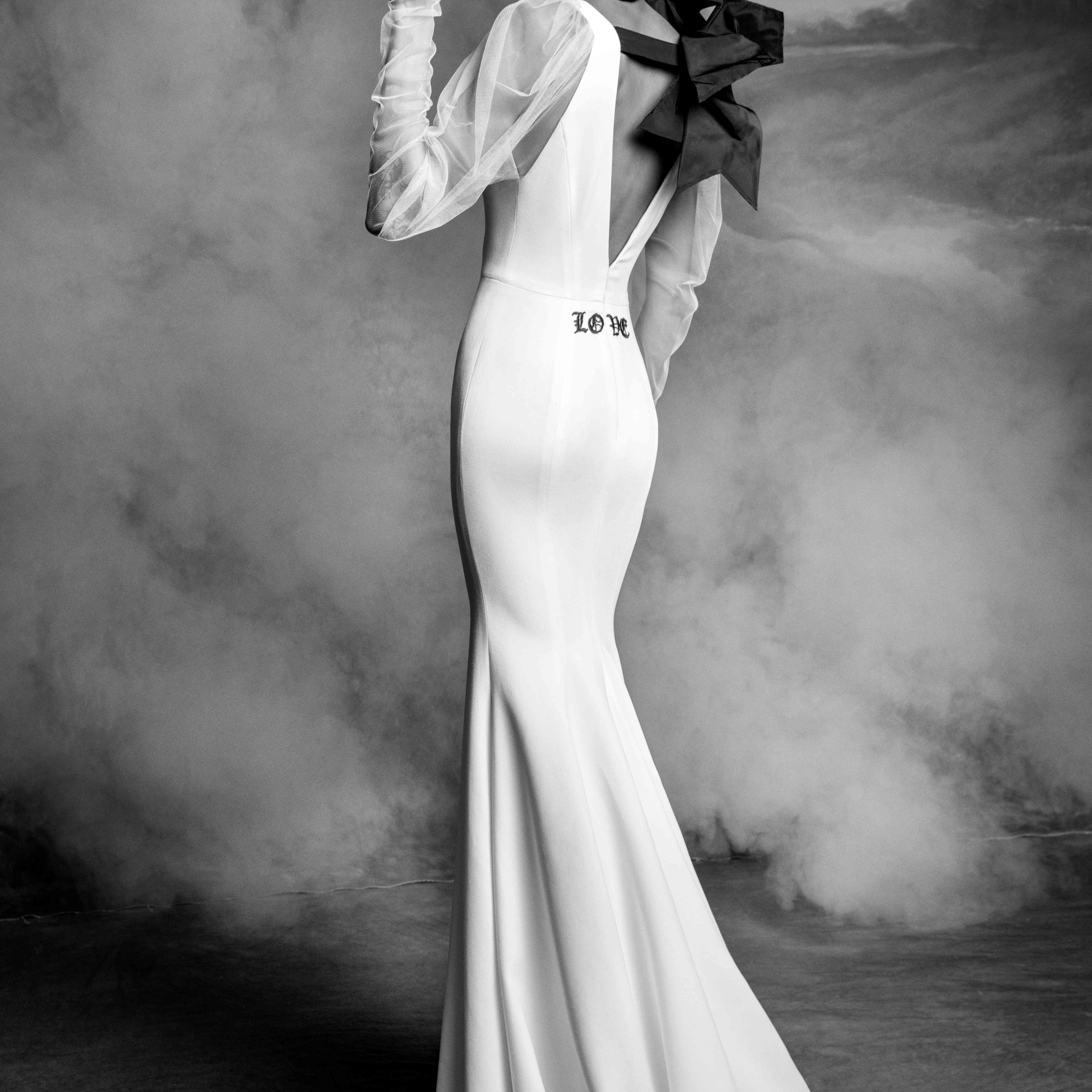 Model in plunging mermaid gown with draped tulle sleeves with a black architectural bow detail and