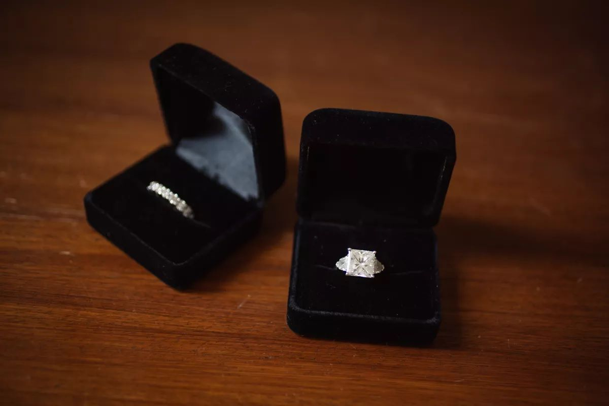 Princess cut engagement ring in ring box and diamond wedding band in ring box beside it