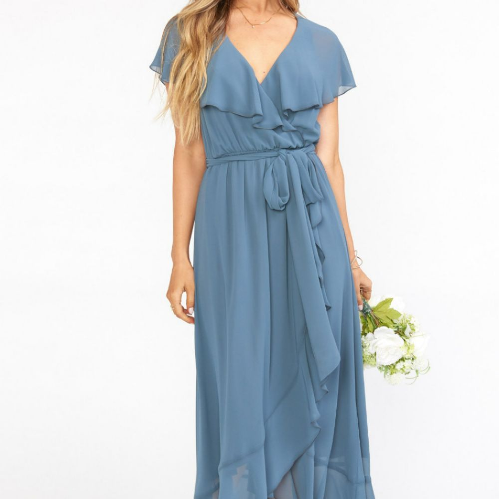 Model in a light blue ruffled gown with a high-low hem and flutter sleeves, with a tie at the waist