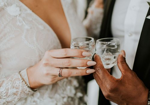 Close-up of bride and groom's hand holding skull-shaped shot glasses with clear liquor inside them
