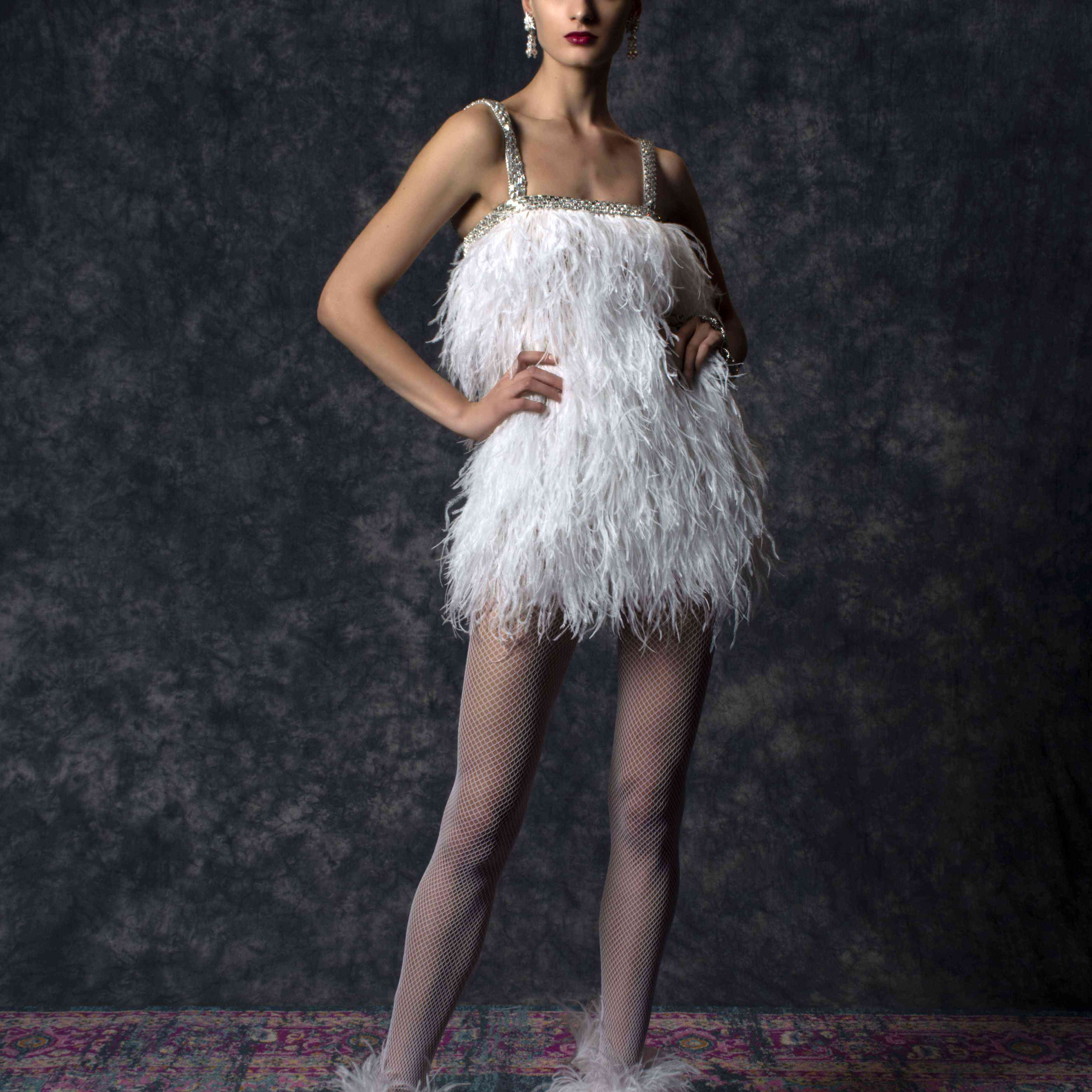 Model in mini feather dress with silver beaded straps