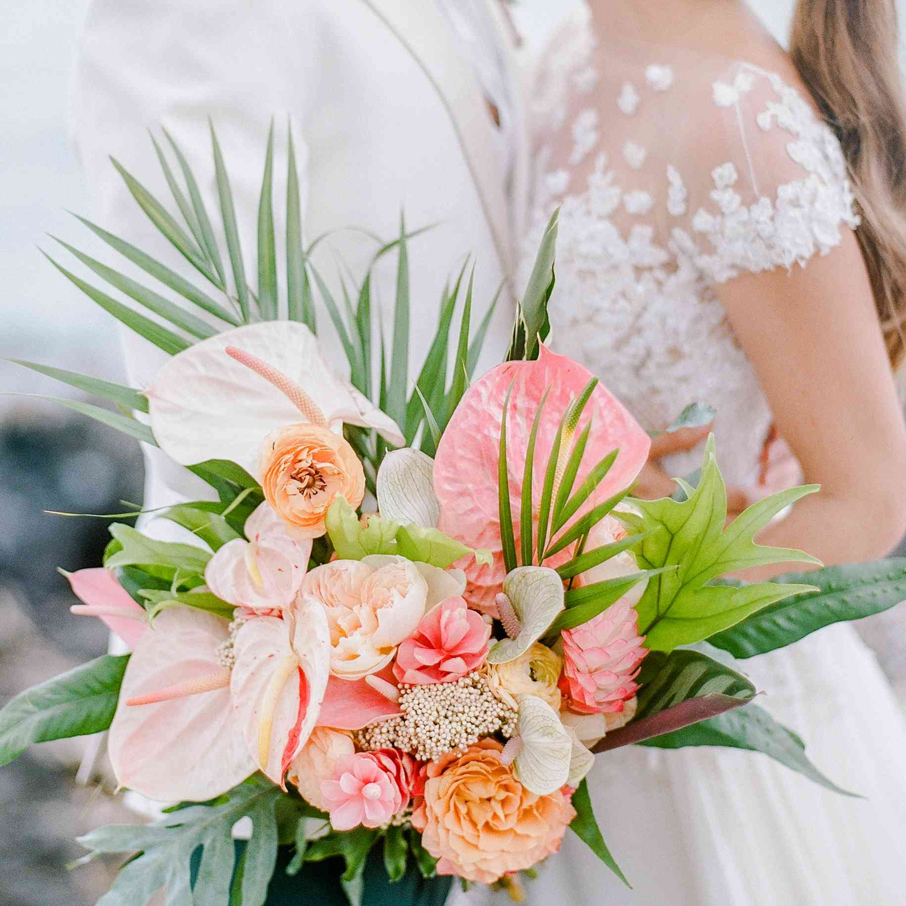 Bride and groom embracing, bride holding tropical flower bouquet