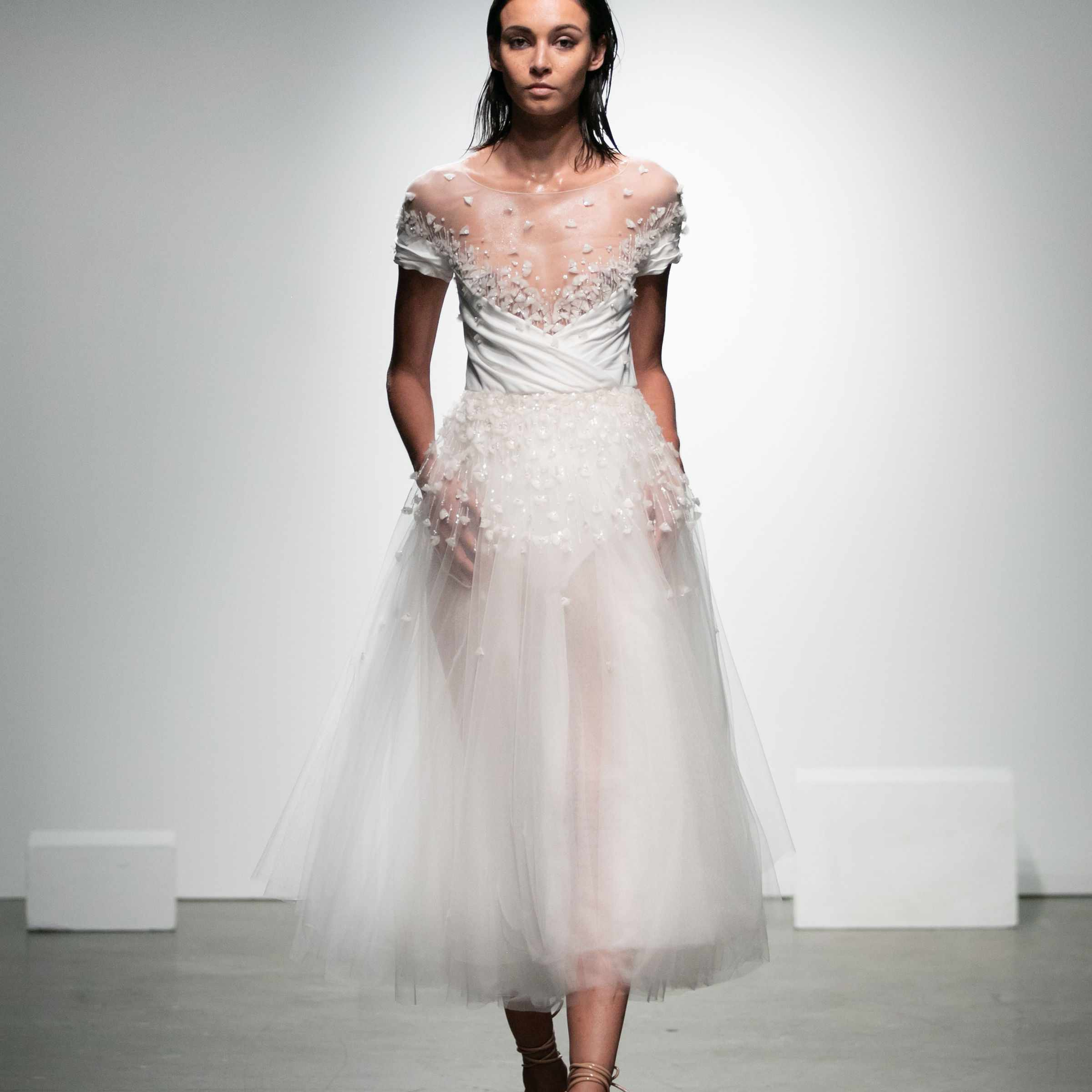 Model in tea-length tulle dress with floral embroidery and short sleeves