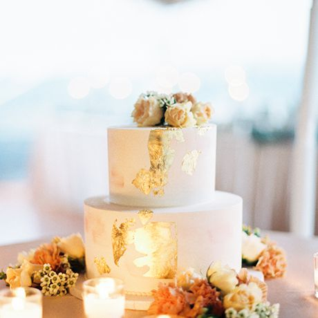 A simplistic-chic wedding cake with metallic gold foil and a floral cake topper