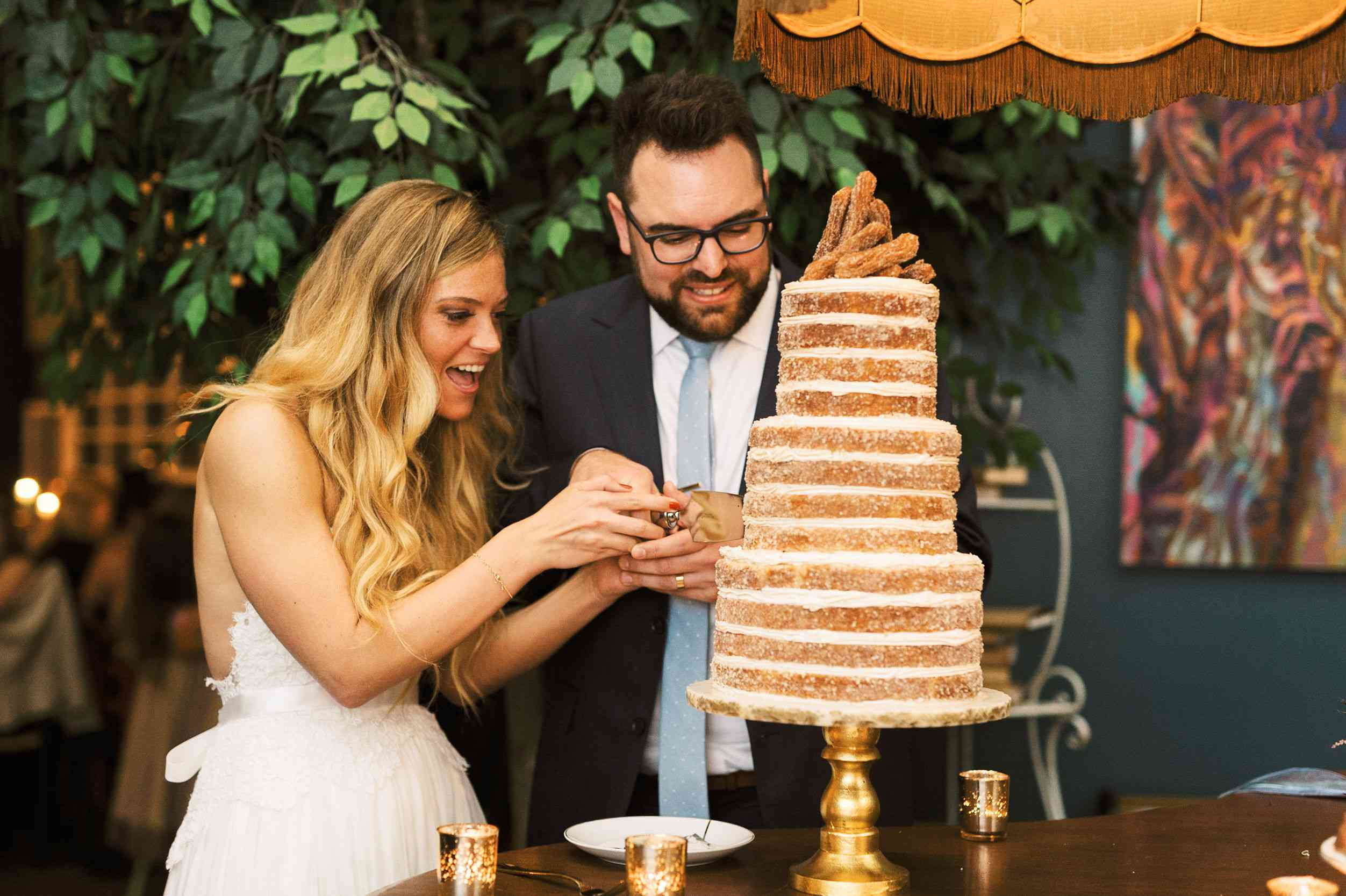 whimsical savannah wedding, bride and groom cutting churro cake