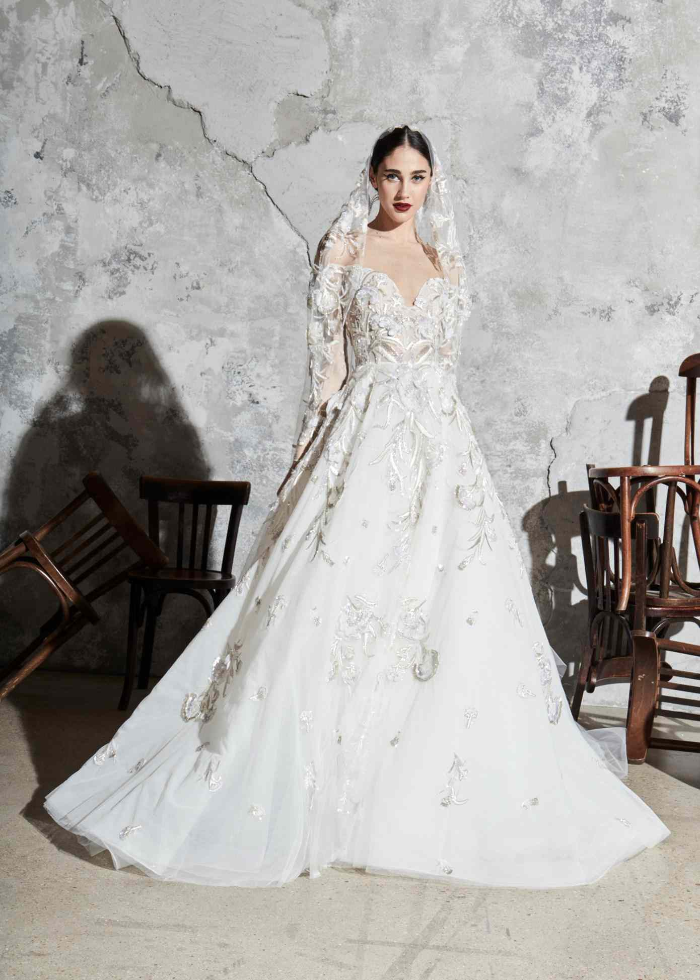 Model in off-the-shoulder long-sleeve ballgown with deep sweetheart neckline and silver and gold embroidery with a matching veil