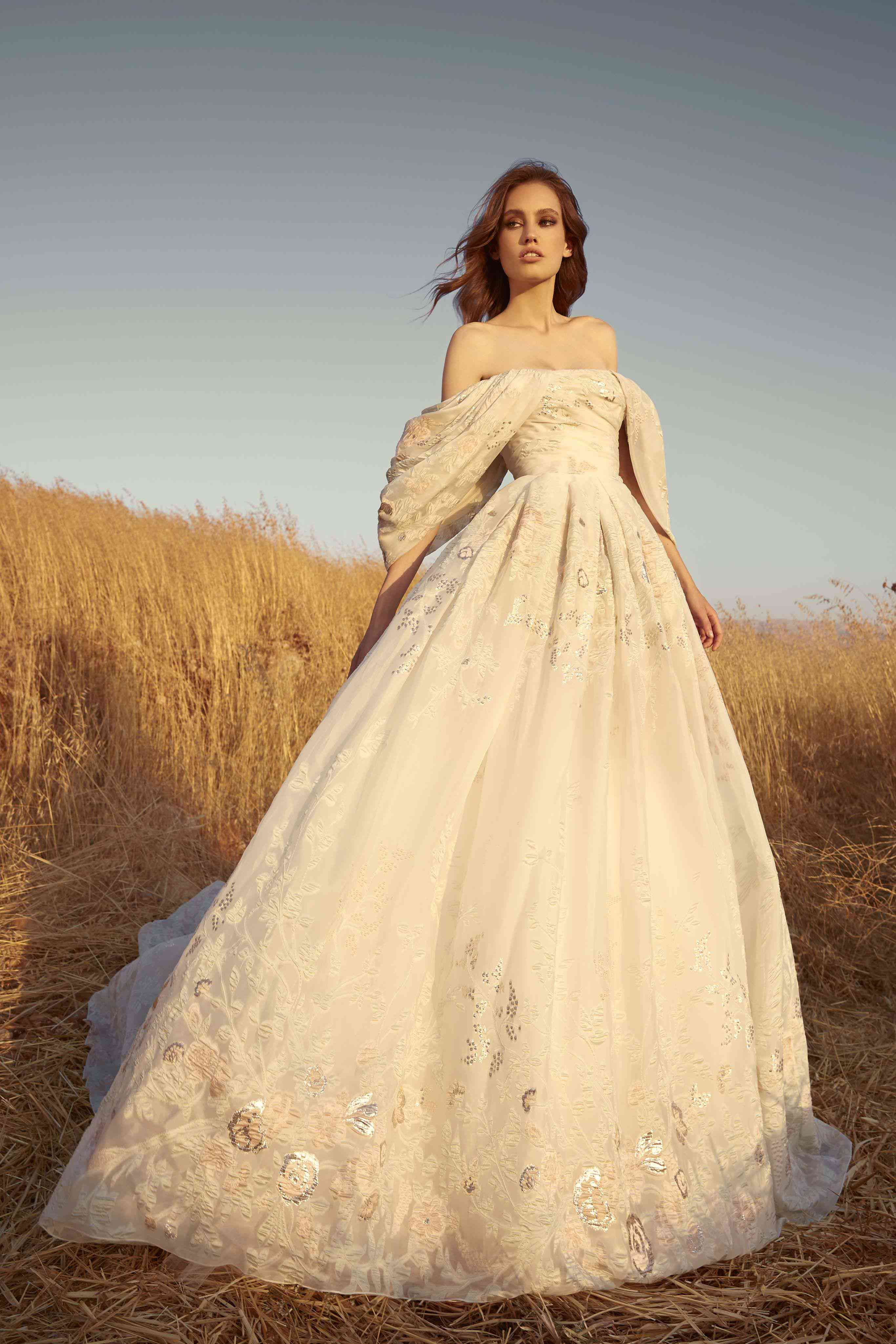 Model in a draped strapless dress of pastel multi-colored embroidery and off-shoulder dropped sleeves