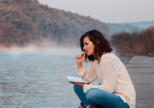 Woman sitting on a dock on the water with a notebook and a pen, thinking