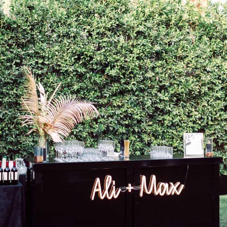Glam bar with gilded palm fronds and custom neon sign