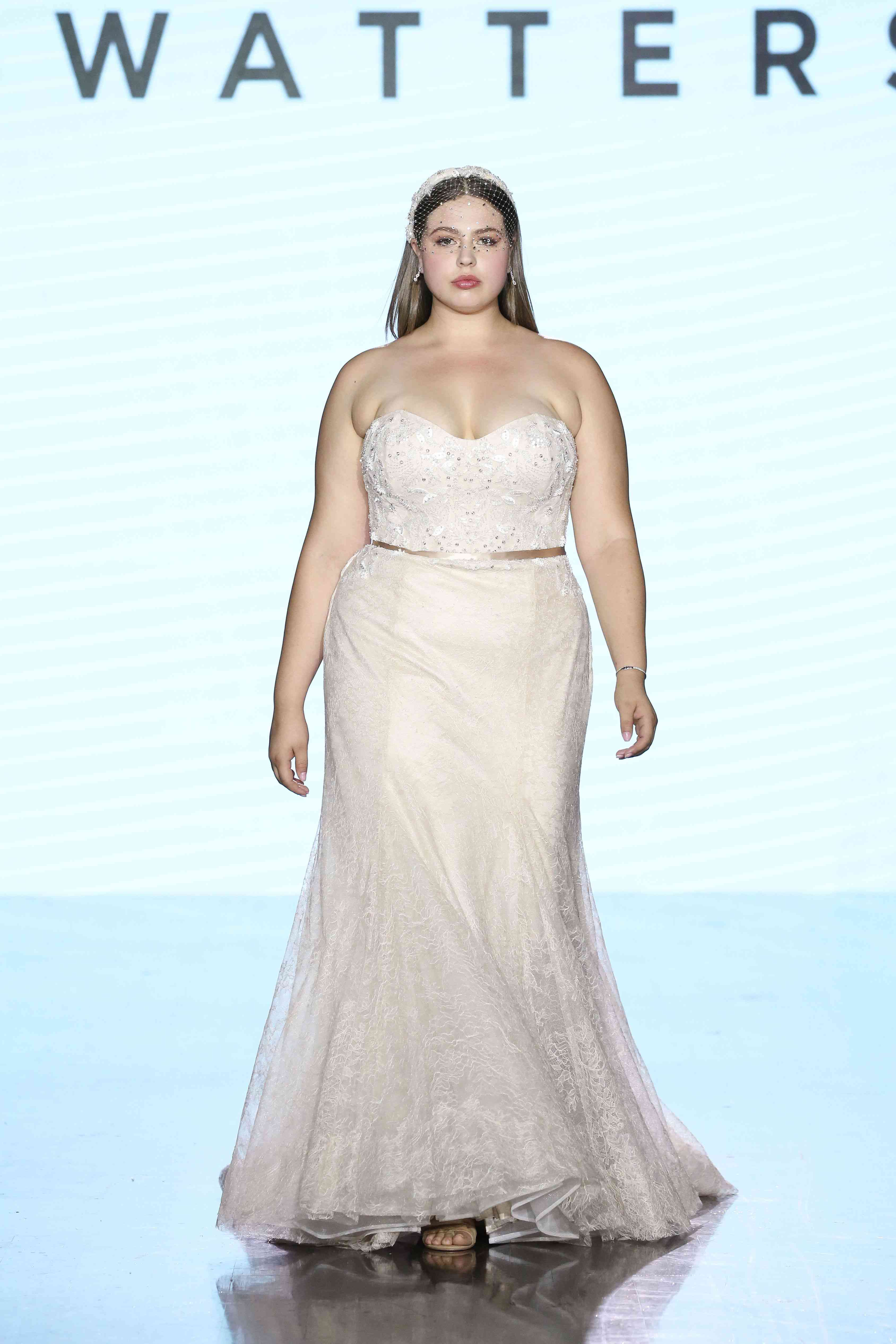 Model on runway in strapless lace trumpet gown