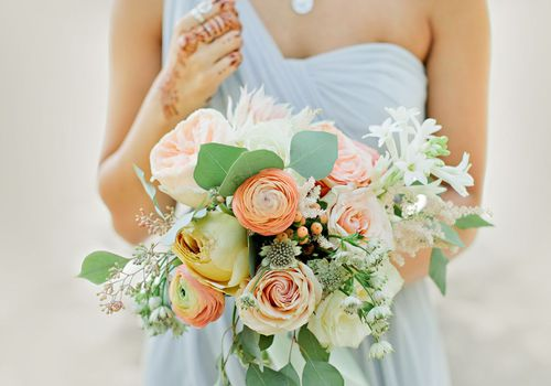 Bride holding a bouquet with peach and white flowers