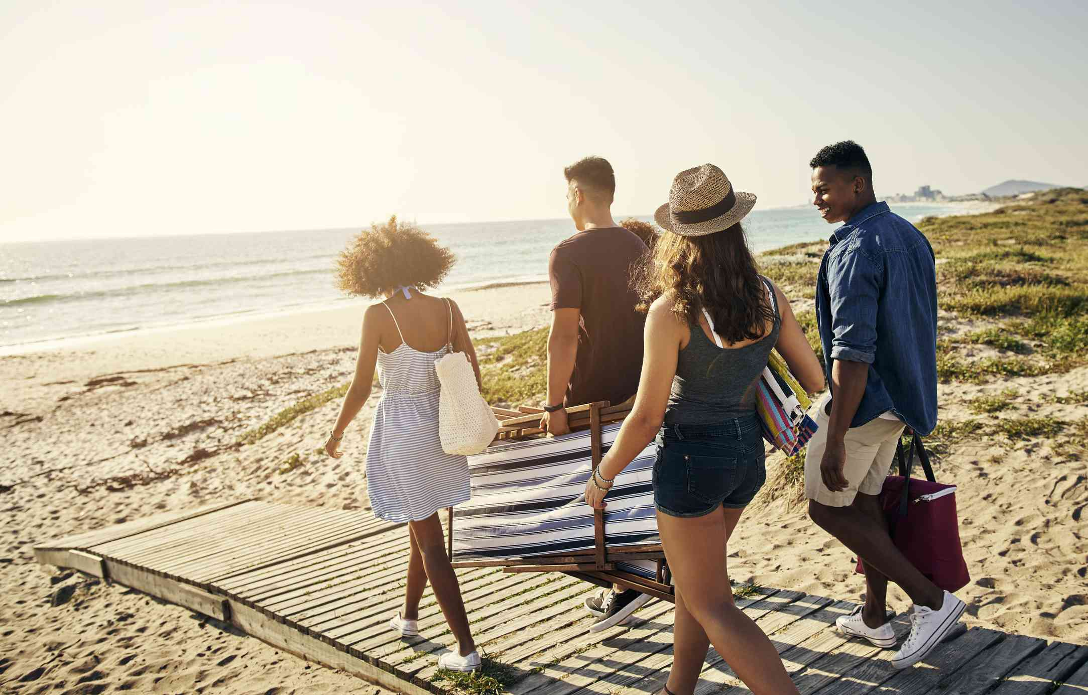 Four friends walking onto the beach