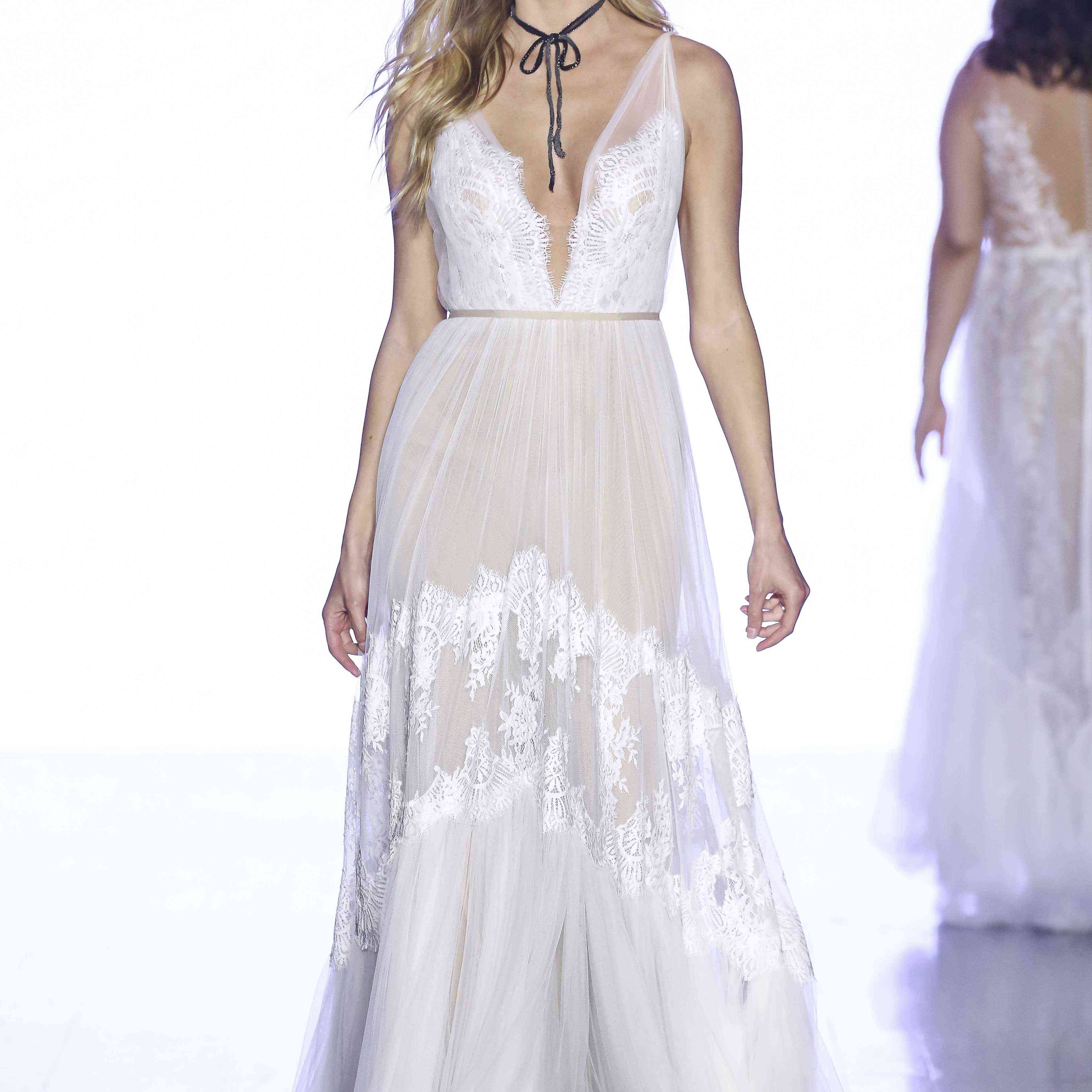 Model in V-neck gown with lace bodice and tulle and lace skirt