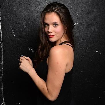 Headshot of Léa Rose Emery against black wall