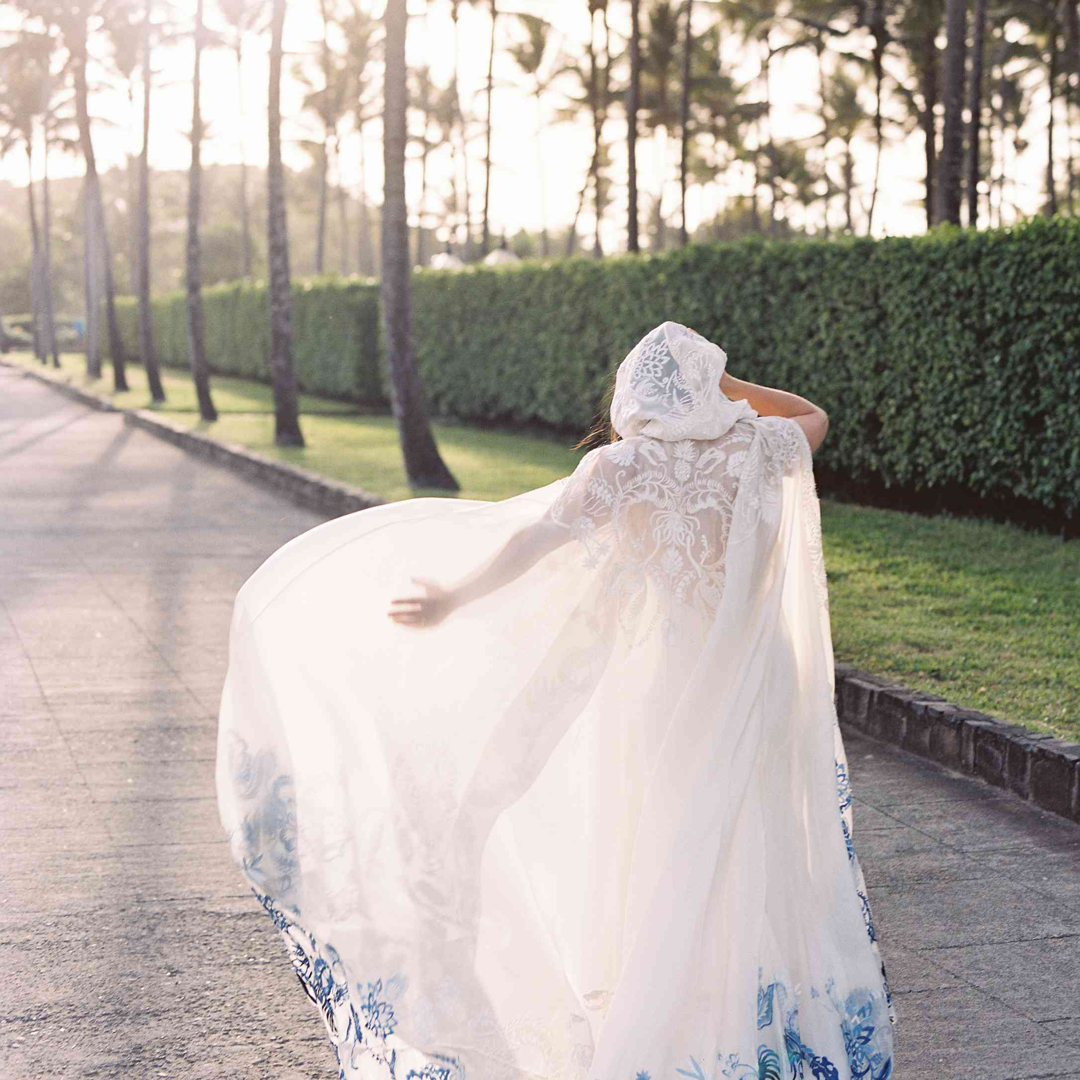 back of brides dress with cape and blue embroidery