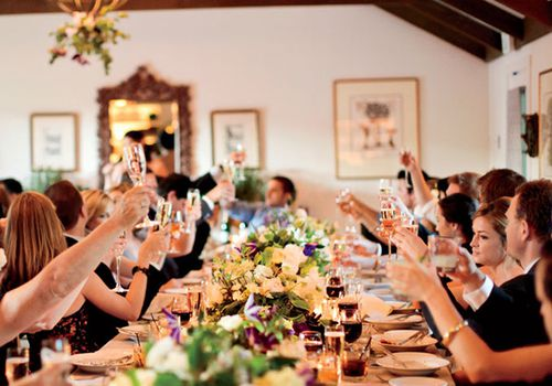 guests around a table during a toast at a wedding