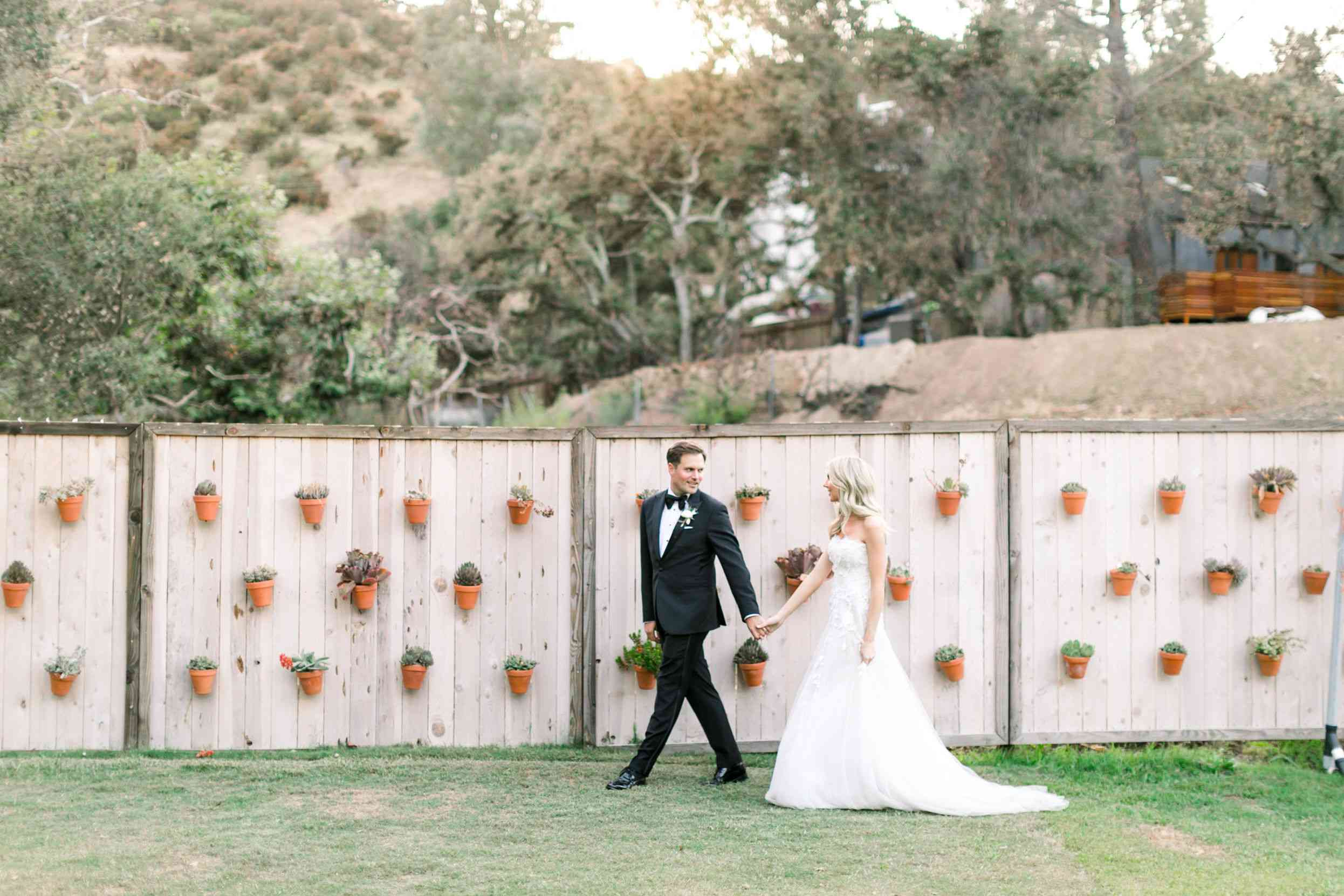 couple walking in front of wall of potted plants