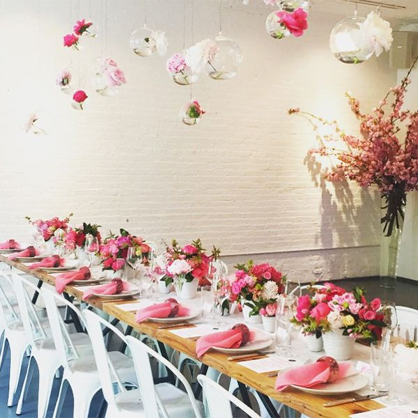 Rectangular table set with pink napkins and pink bouquets