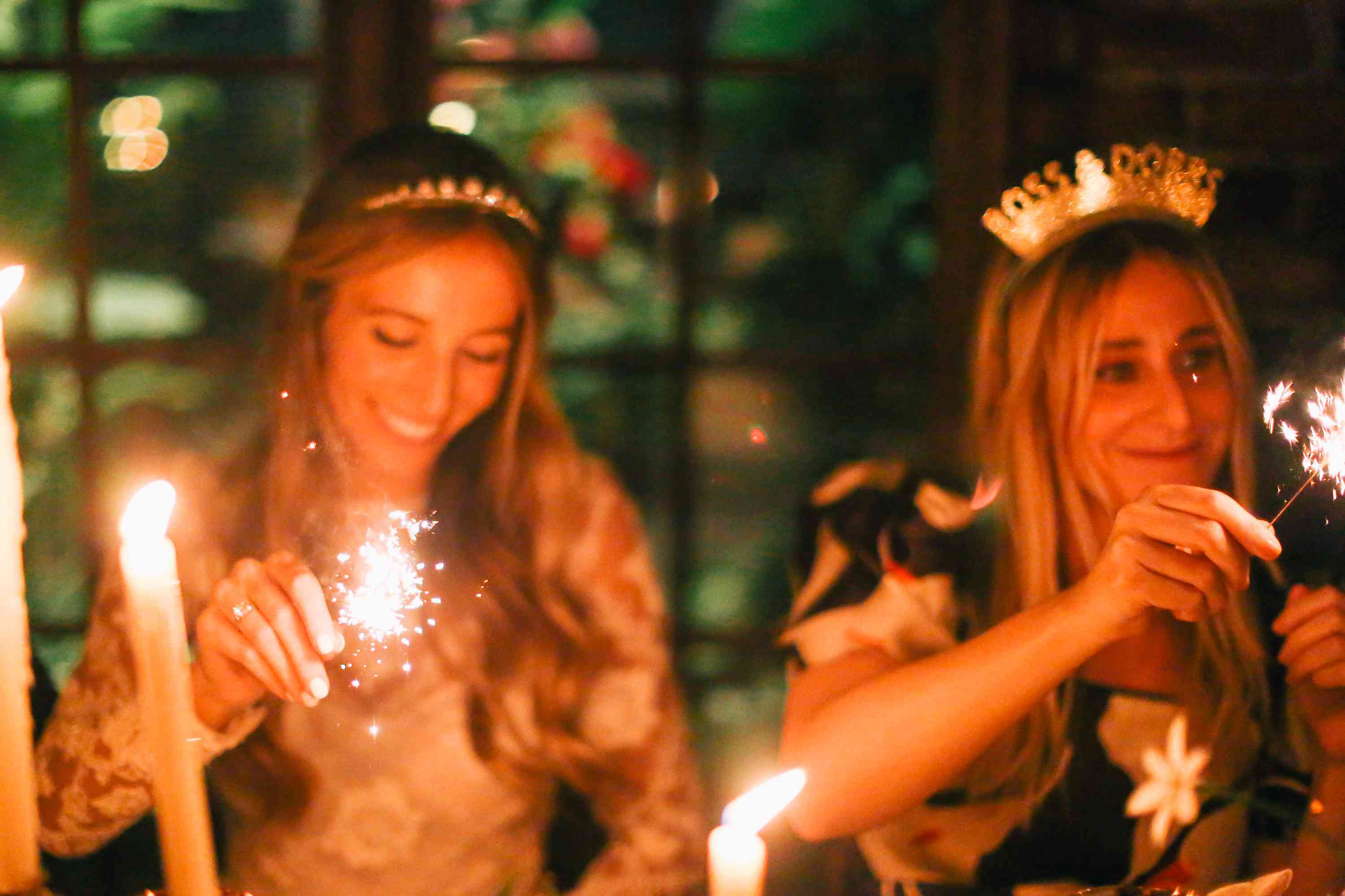 Bride and wedding guest waving sparklers