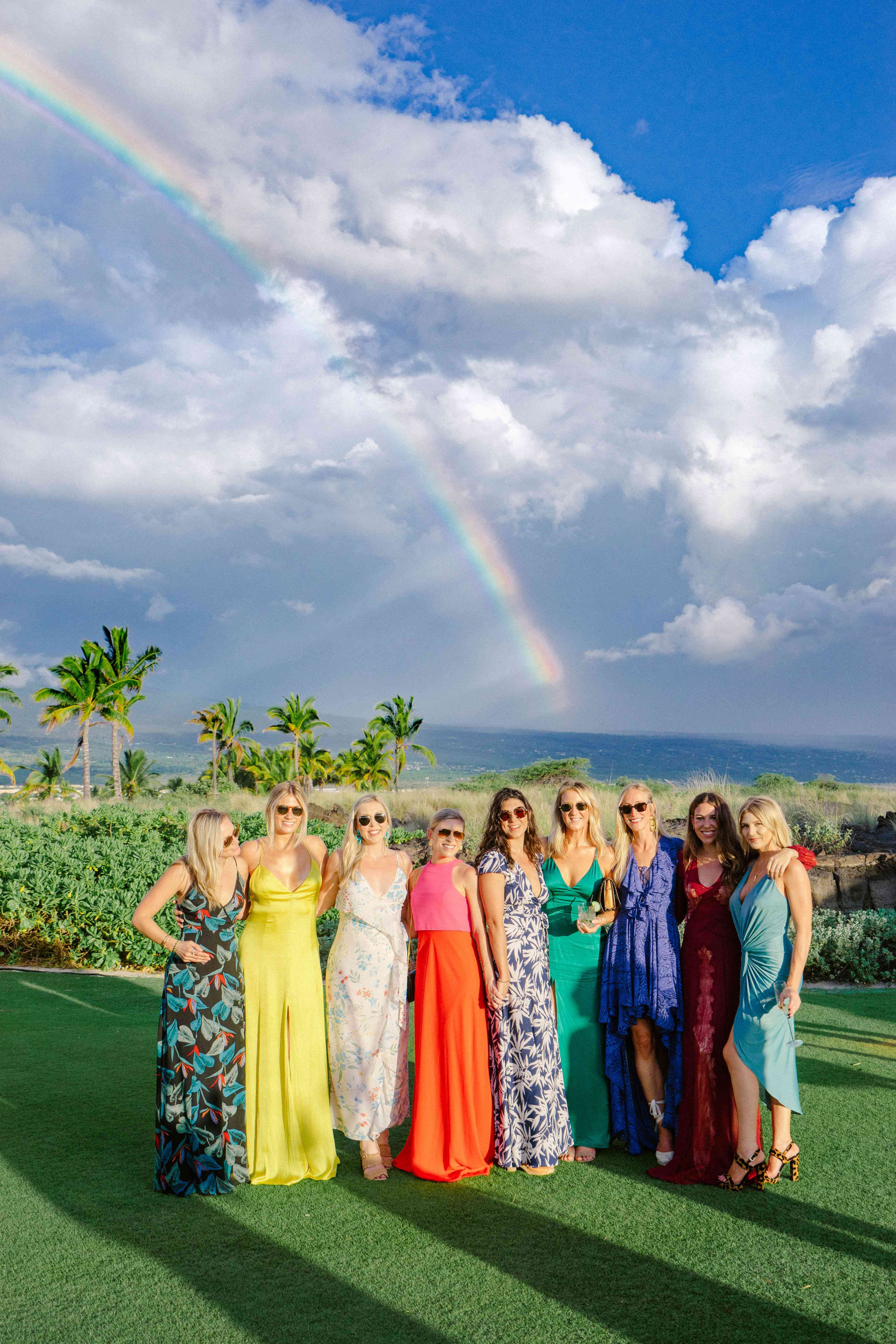 Wedding guests pose in front of the rainbow