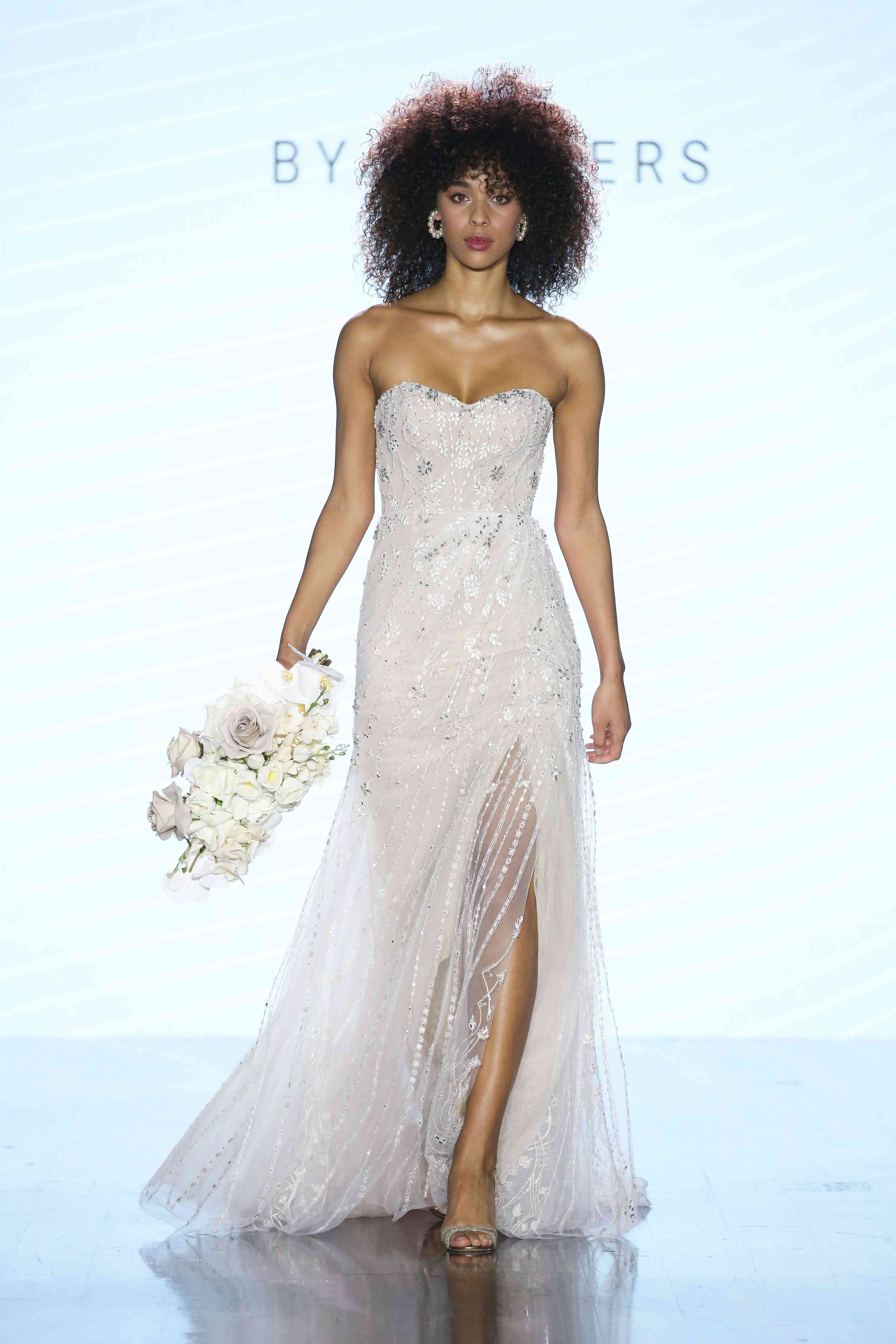 Model in strapless sweetheart wedding gown with allover silver beading and a front slit