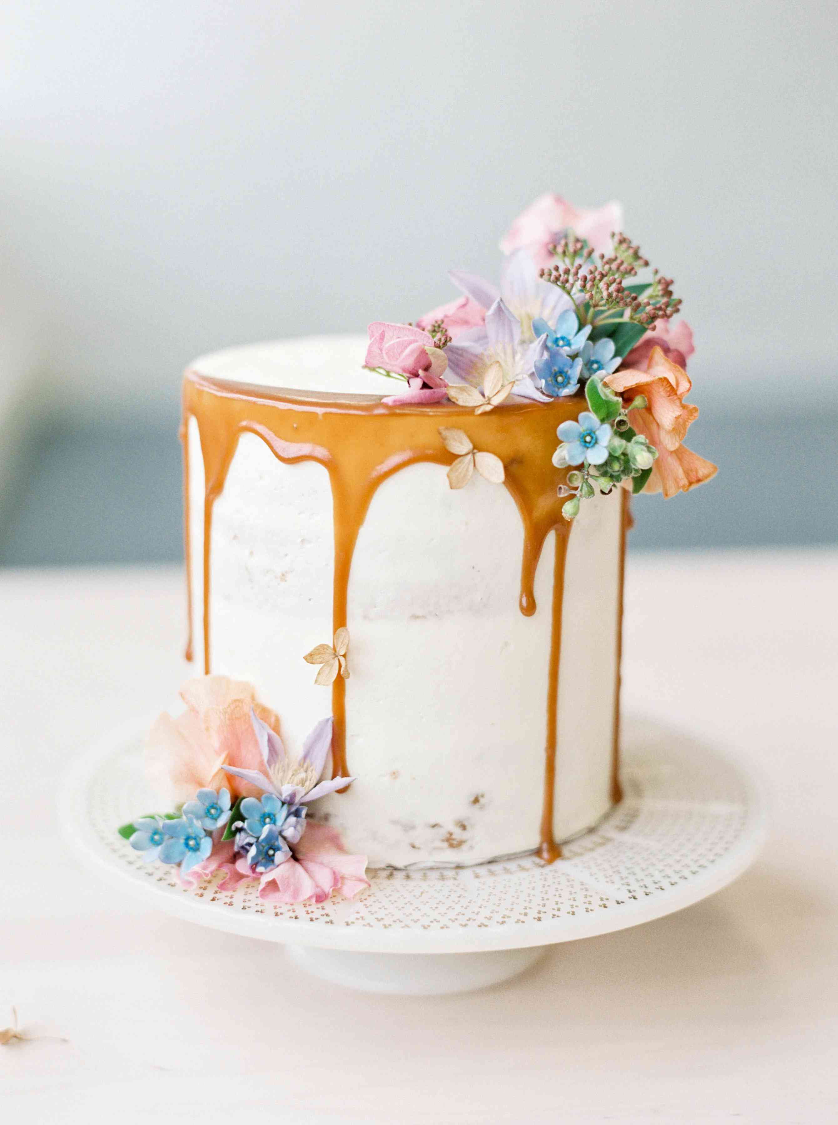 A one tiered white drip cake decorated with flowers