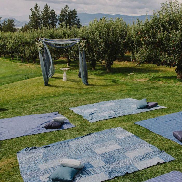 Blankets and pillows scattered in a grassy field