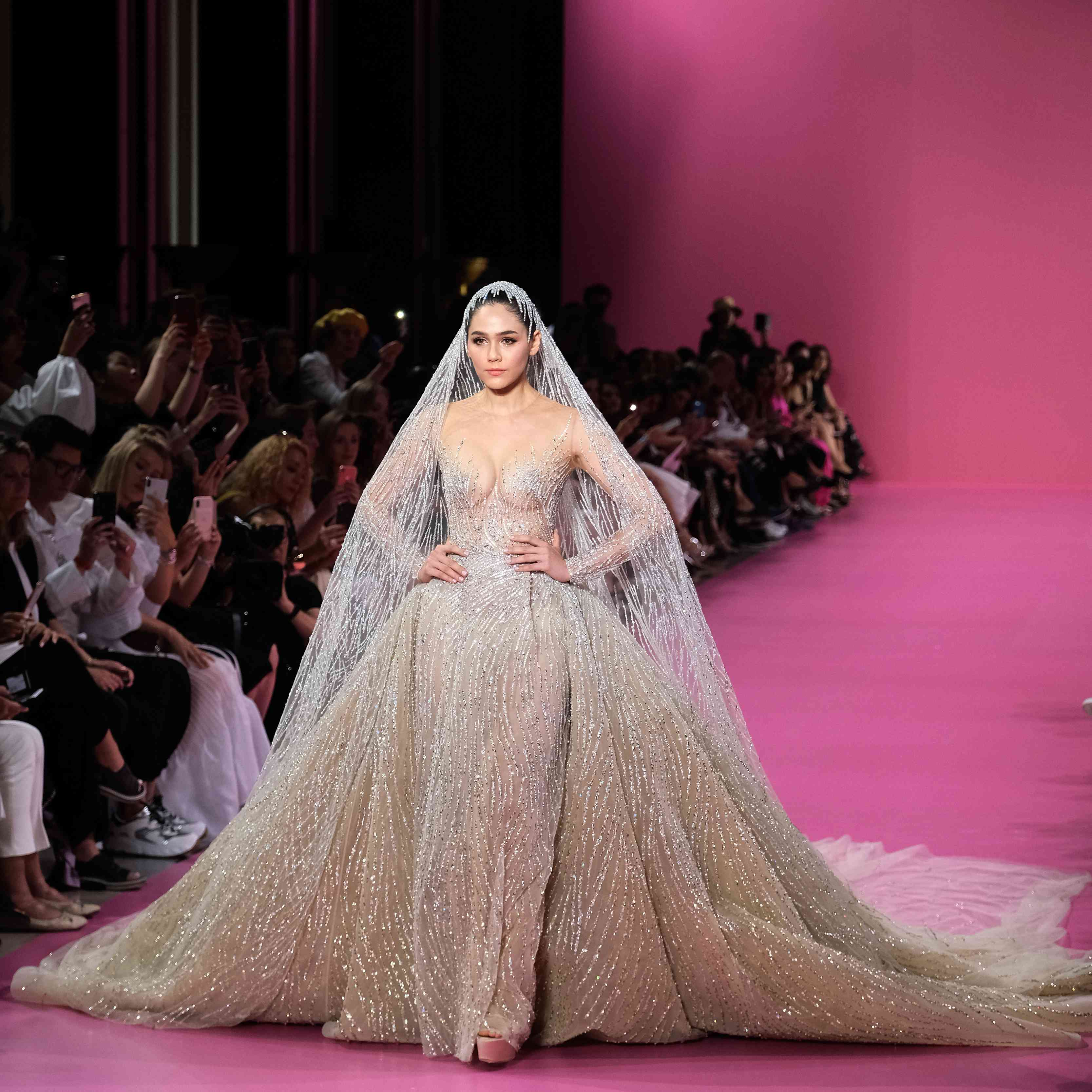 Model in gold princess gown with large skirt and long veil