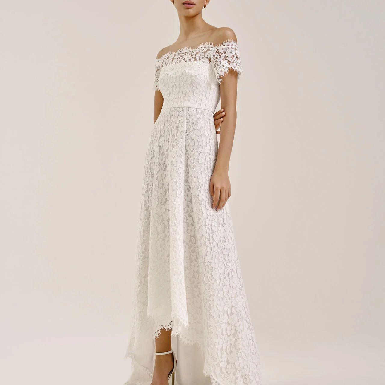 Model in lacy off-the-shoulder wedding dress with subtle high-low hem