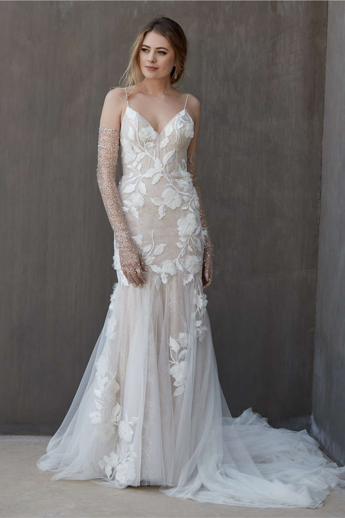 Model in spaghetti strap trumpet gown with allover floral embroidery and a tulle skirt